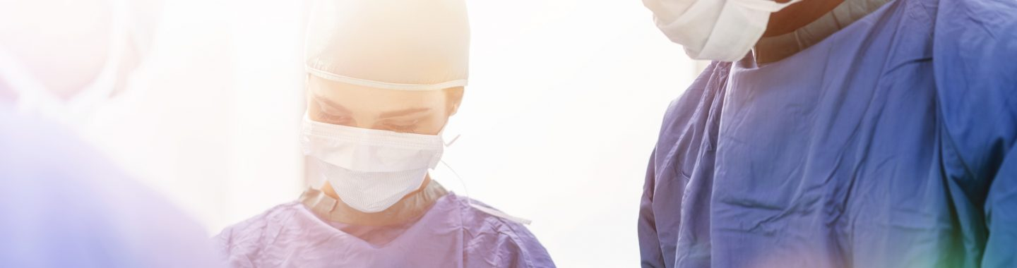 3 doctors with face masks on working on patient