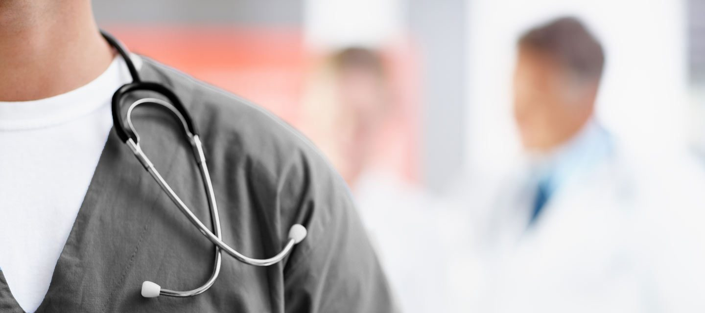 Closeup of man in gray Avala scrubs with name-tag and stethoscope.